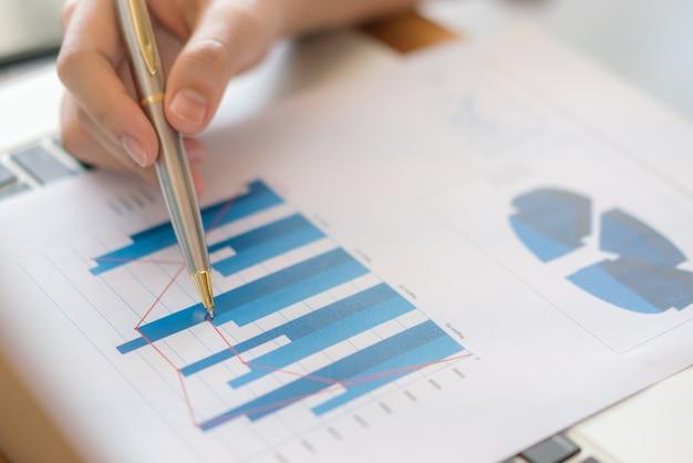Business vrouw hand met financial charts en laptop op de tafel.