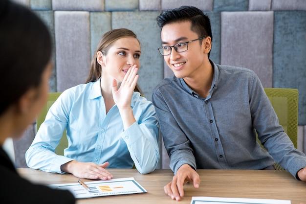 Business woman whispering geheim aan mannelijke collega