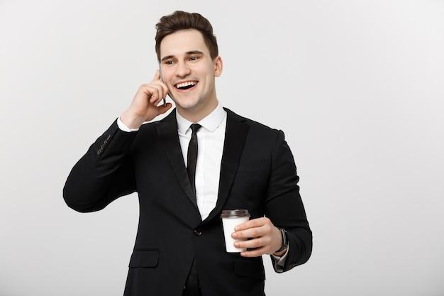 Businessconcept: close-up zelfverzekerde jonge knappe zakenman praten op mobiele telefoon en koffie drinken over witte geïsoleerde achtergrond.