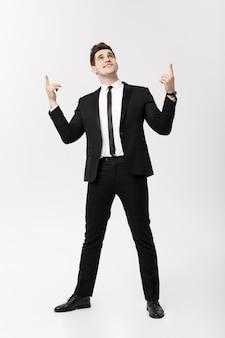Businessconcept: knappe man gelukkig glimlach jonge knappe kerel in slim pak poseren wijzende vinger over geïsoleerde grijze achtergrond.