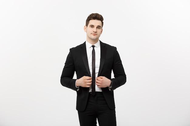 Businessconcept: knappe man gelukkig glimlach jonge knappe kerel in slimme pak poseren over geïsoleerde grijze achtergrond.