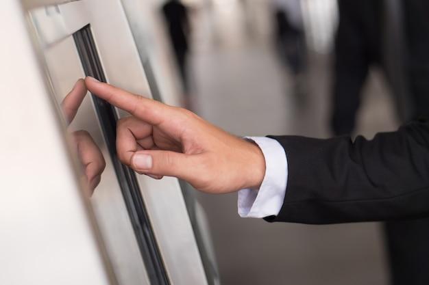 Businessmans hand aanraken of met behulp van metro ticketautomaat