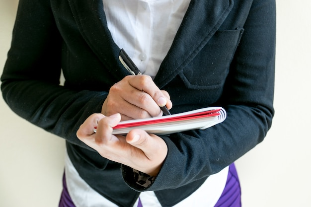 Bussiness vrouw die het woord op een notitieboekje schrijft.