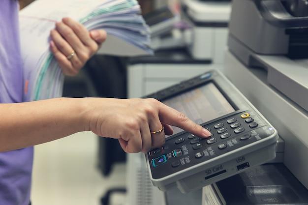 Bussinesswoman die kopieerapparaatmachine gebruiken om administratie te kopiëren.