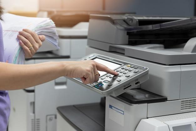 Bussinesswoman die kopieerapparaatmachine gebruiken om hoop van administratie in bureau te kopiëren.