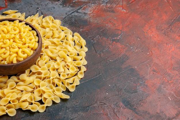 Butterfly ongekookte pasta's in een bruine kom op gemengde kleurentafel
