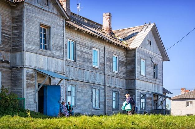 Buurtbewoners van de solovetsky-eilanden zitten op een bank bij een houten huis met twee verdiepingen in het dorp