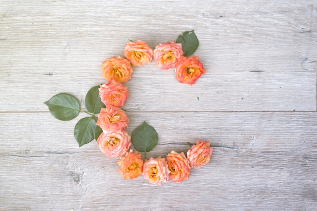 C, het alfabet van de rozenbloem dat op grijze houten vlakke achtergrond wordt geïsoleerd, legt