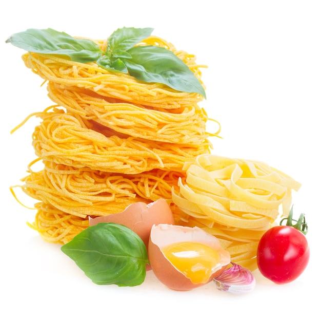 C rauwe pasta met ei en tomaat geïsoleerd op wit