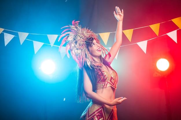 Cabaret, danseres en vakantieconcept - leuk jong meisje in helder kleurrijk carnaval-kostuum op donker