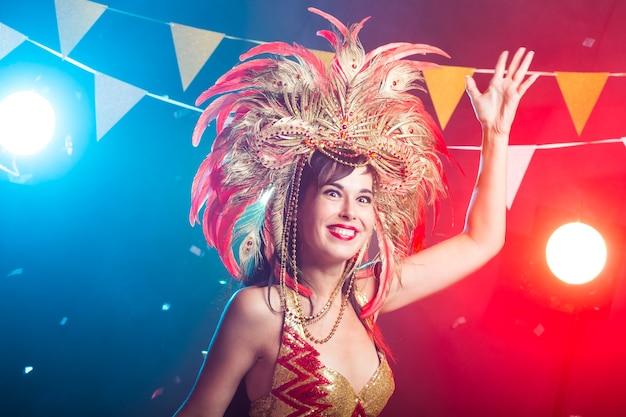 Cabaret, danseres en vakantieconcept - leuk jong meisje in helder kleurrijk carnaval-kostuum op donkere muur.