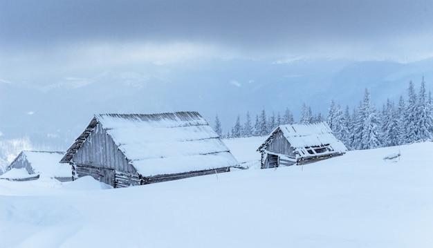 Cabine in de bergen in de winter. mysterieuze mist. in afwachting van vakantie. karpaten. oekraïne, europa