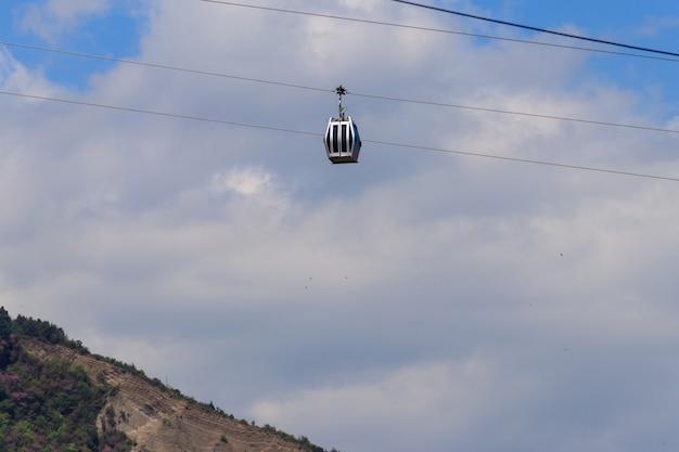 Cabine van de kabelbaan tegen blauwe hemel. kabelbaan in tbilisi, georgië