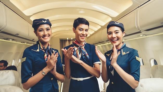Cabinepersoneel klappen handen in vliegtuig. luchtvaartmaatschappij transport en toerisme concept.