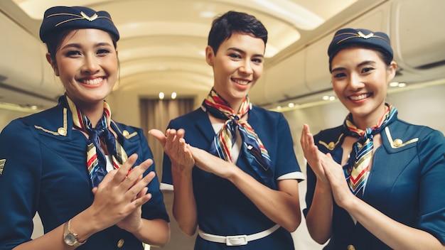 Cabinepersoneel klappen handen in vliegtuig