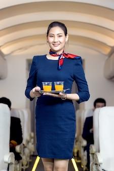 Cabinepersoneel serveert water aan passagiers in vliegtuig. luchtvaartvervoer en toerismeconcept.