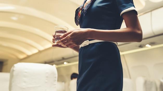 Cabinepersoneel serveert water aan passagiers in vliegtuig