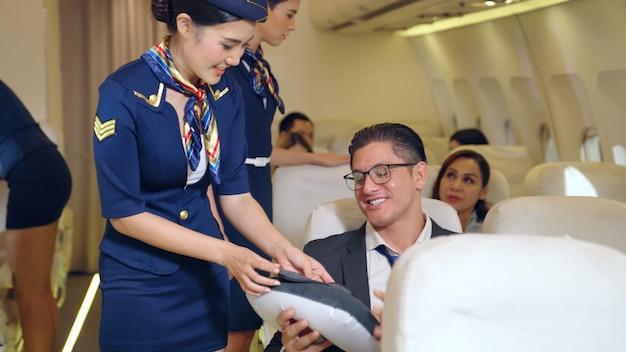 Cabinepersoneel verleent service aan passagiers in vliegtuig. luchtvaartvervoer en toerisme concept.