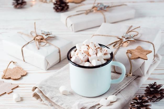 Cacao en marshmallows in een mok naast ambachtelijke geschenken op een witte houten tafel. warme zoete dranken