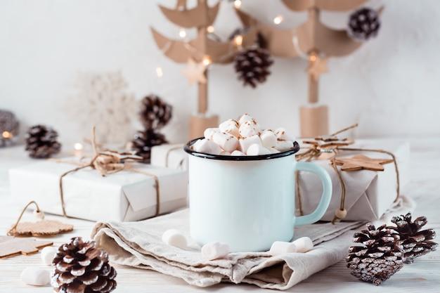 Cacao en marshmallows in een mok naast ambachtelijke geschenken tegen de achtergrond van kartonnen kerstbomen op een witte houten tafel. warme zoete dranken