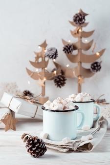 Cacao en marshmallows in mokken, ambachtelijke kerstcadeaus en kerstbomen op een witte houten tafel. milieuvriendelijke vakantie. verticale weergave