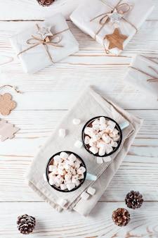 Cacao en marshmallows in mokken en ambachtelijke kerstcadeaus op een witte houten tafel. milieuvriendelijke vakantie. boven- en verticaal aanzicht