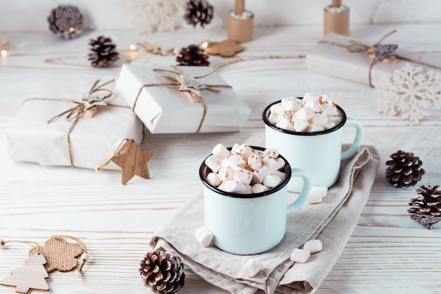 Cacao en marshmallows in mokken en ambachtelijke kerstcadeaus op een witte houten tafel. milieuvriendelijke vakantie