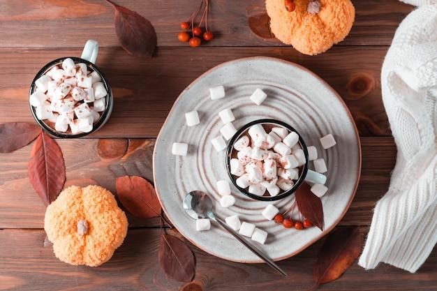 Cacao en marshmallows in mokken in herfstdecoraties met pompoenen op een houten tafel. warme zoete dranken. bovenaanzicht