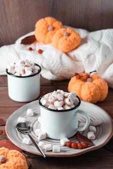 Cacao en marshmallows in mokken in herfstdecoraties met pompoenen op een houten tafel. warme zoete dranken. verticale weergave