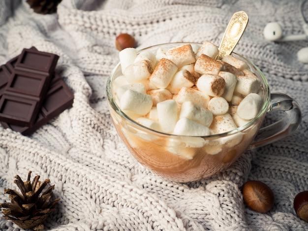 Cacao in een glazen beker met een marshmallow, chocoladekaneelkegels en noten