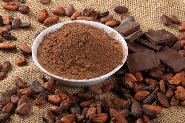 Cacao in poedervorm met stukjes chocolade op rauwe cacaobonen.