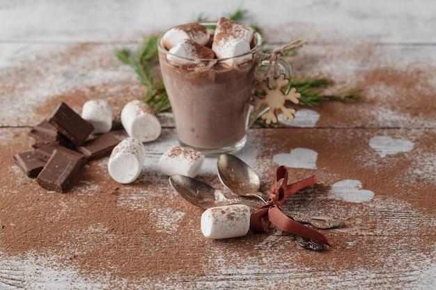 Cacao of latte of warme chocolademelk met marshmallow en op smaak gebracht met kaneel. op een houten tafel. kerstcadeau