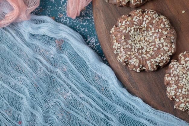 Cacao sesamkoekjes op rustieke houten bord.
