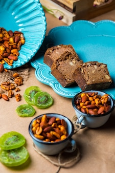 Cacao walnotenbrood in turquoise plaat geserveerd met gedroogde kiwi's en noten