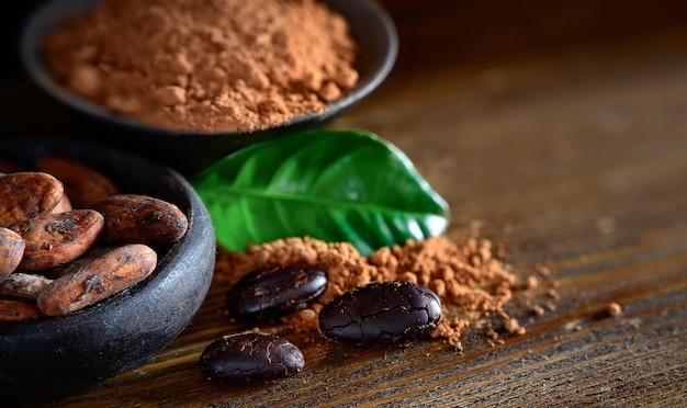 Cacaobonen en poeder in kom met bladeren op houten tafel
