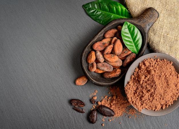 Cacaobonen en poeder in oude houten kom met groene bladeren