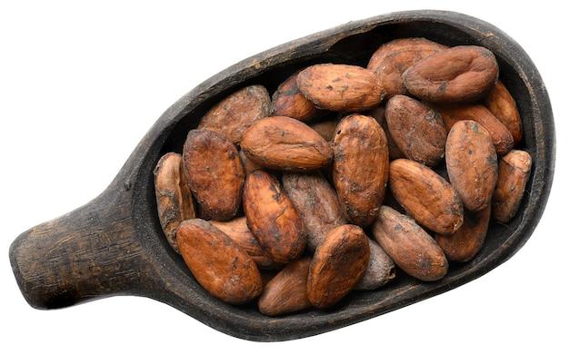 Cacaobonen in oude houten kom die op wit wordt geïsoleerd