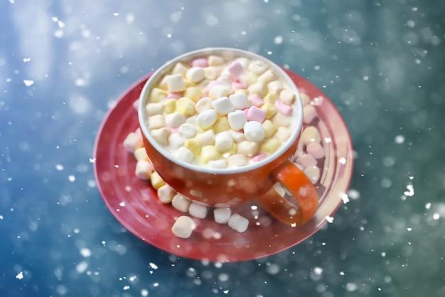 Cacaodrank met marshmallows in beker van rood keramiek sneeuwvaleffect