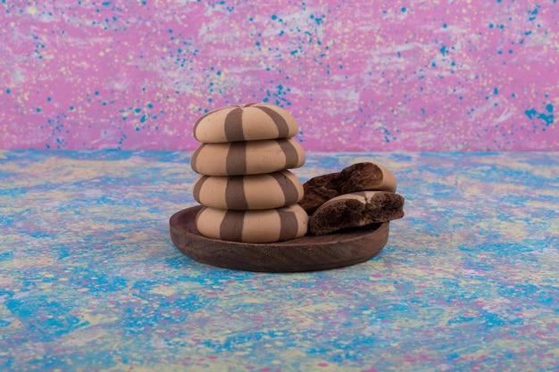 Cacaokoekjes in een houten schotel op blauw