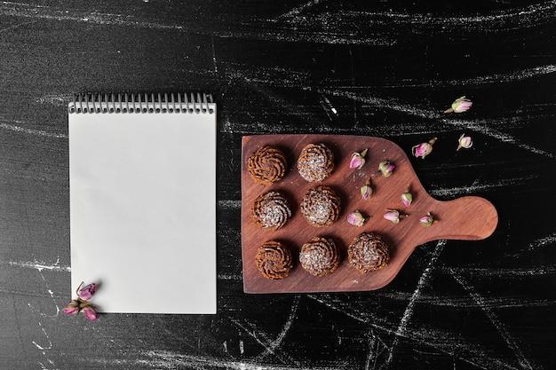 Cacaokoekjes op een houten bord met een receptenboek opzij.