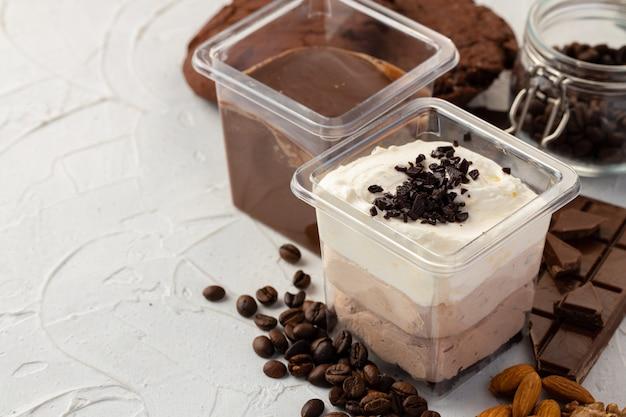 Cacaomousse dessert in transparante plastic doos op grijze ondergrond