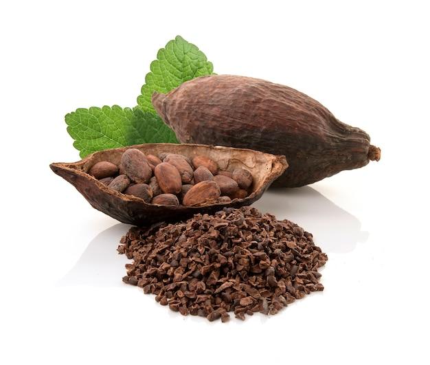 Cacaopeulen en cacaobonen en cacaopoeder met bladeren op witte achtergrond worden geïsoleerd die