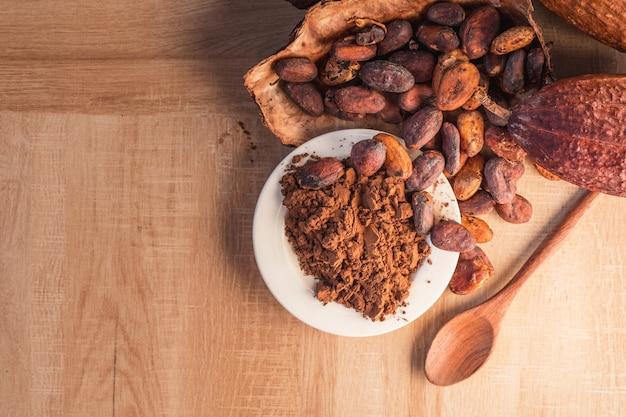 Cacaopoeder en cacaobonen met cacao peulen op houten achtergrond.