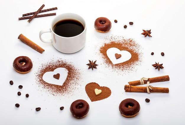 Cacaopoeder in de vorm van hart, muntstengels en een kopje espresso met chocoladedoughnuts.