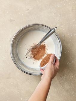 Cacaopoeder wordt toegevoegd aan de opgeklopte eieren en suiker in een metalen kom op beige kleur keukentafel, bovenaanzicht