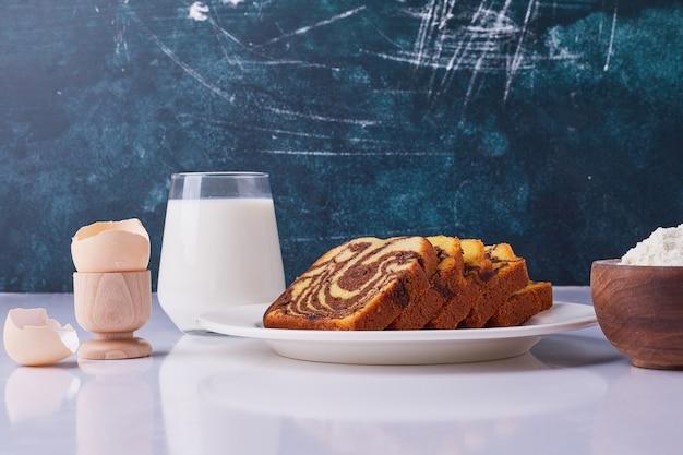 Cacaotaart gesneden en geserveerd in een witte keramische plaat met ingrediënten rond.