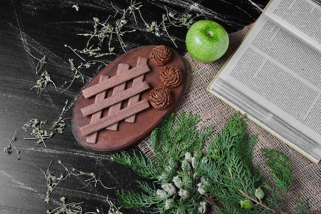 Cacaowafels op een rustieke achtergrond met koekjes.