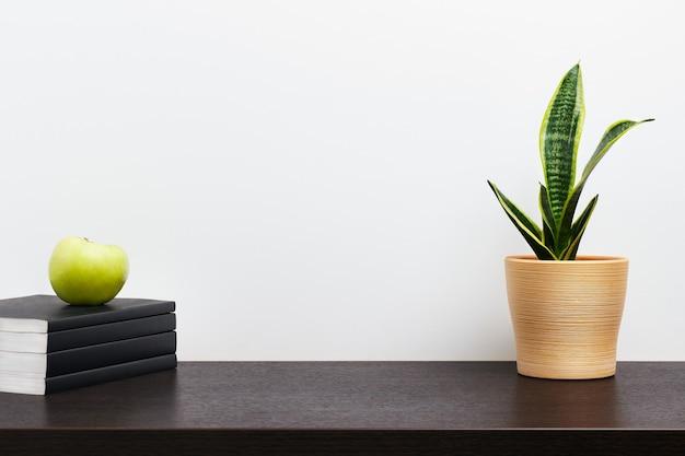 Cactus in een gele pot en boek op donkere werkruimtetafel en witte muurachtergrond