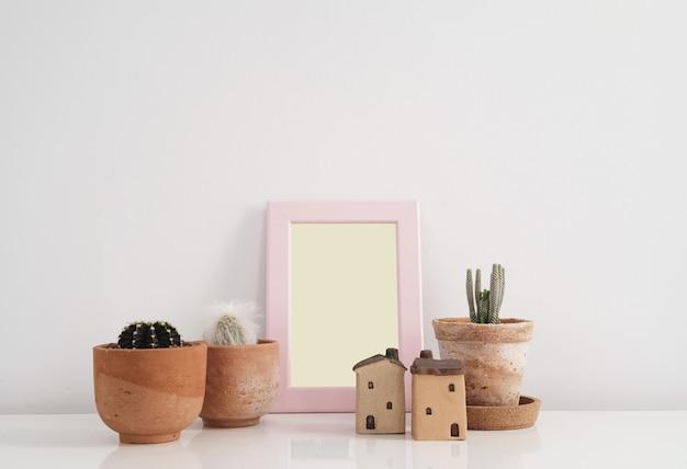 Cactus in kleipot met lege fotokaderachtergrond.