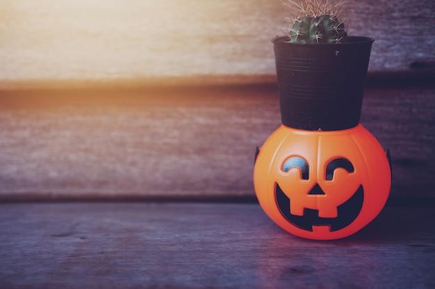 Cactus in zwarte pot op halloween-pompoenhoofd met gouden licht in donkere nacht